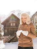 Happy woman writing sms while standing near cosy mountain house