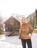 Happy young woman standing in the front of cosy mountain house