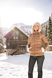 Relaxed woman standing in the front of a cosy mountain house
