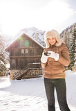 Woman standing near mountain house and checking photos in camera
