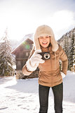 Woman standing near mountain house and taking photos with camera
