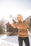 Woman standing in front of mountain house and taking selfie
