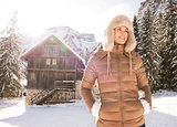 Happy young woman standing in the front of a cosy mountain house