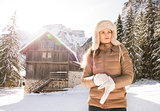 Woman adjusting glove while standing in front of mountain house