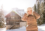Woman adjusting fur hat while standing near cosy mountain house