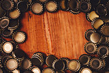 Beer bottle caps frame over wooden background