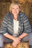 Middle Aged Blond Woman Sitting on Hay Bale