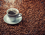Hot aromatic coffee drink in the white cup with beans background