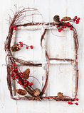 Wooden frame window with red berries, hawthorn, snow and cones Christmas Happy New Year background