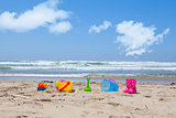 Colorful plastic beach toys lying on the beach sand