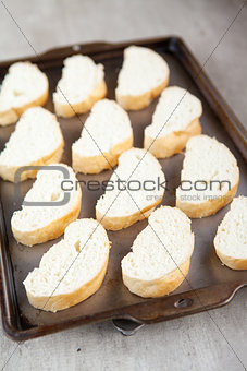 Slices of french bread loaf on baking tray