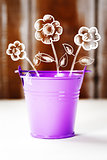 Spring concept with purple bucket and flowers