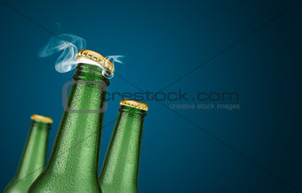 Three green beer bottles on blue background
