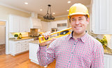 Contractor with Level Wearing Hard Hat Standing In Custom Kitchen