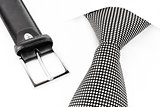 black and white spotted tie knotted Windsor and leather belt