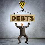 Businessman holding heavy word debts