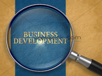 Business Development through Loupe on Old Paper.