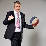 Business man playing with a basketball at the studio