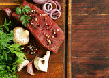 Fresh raw beef meat on a cutting board with vegetables and spices