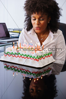Business Woman Celebrating Birthday Party In Office Blowing Cand