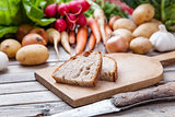 Freshly cut bread on chopping board with organic vegetables