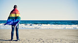 man wrapped in a rainbow flag in front of the ocean