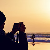 young man taking a picture in front of the sea at dusk