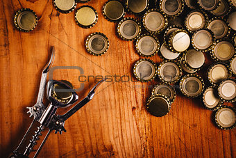 Classic bottle opener and pile of beer bottle caps