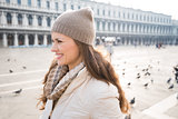 Portrait of happy young woman on Piazza San Marco among pigeons
