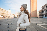 Happy young woman standing on Piazza San Marco and looking aside