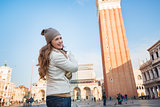 Happy young woman pointing on bell tower of St Mark's Basilica