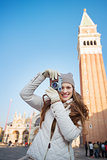 Woman taking photos with camera near Campanile di San Marco