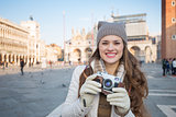 Young woman with retro photo camera on Piazza San Marco