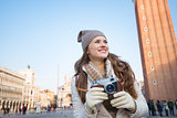 Happy woman holding retro photo camera on Piazza San Marco