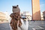 Seen from behind woman with retro camera on Piazza San Marco