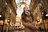 Smiling young woman standing in Galleria Vittorio Emanuele II
