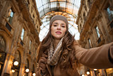 Glamour woman taking selfie in Galleria Vittorio Emanuele II