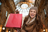 Woman in Galleria Vittorio Emanuele II showing shopping bags