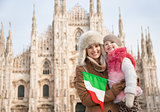 Happy mother and daughter with Italian flag standing near Duomo