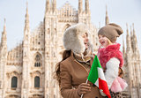 Smiling mother and daughter holding Italian flag near Duomo