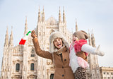Happy mother and daughter with Italian flag rejoicing near Duomo