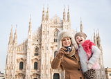 Happy mother and daughter taking photos in front of Duomo, Milan