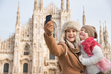 Happy mother and daughter taking selfie in front of Duomo, Milan