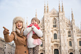 Smiling mother showing something to daughter near Duomo, Milan