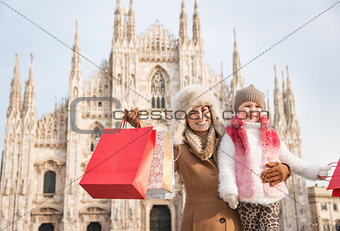 Portrait of mother and daughter with shopping bags near Duomo