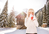 Woman in white sweater enjoying hot beverage near mountain house
