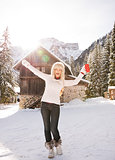 Happy woman with red cup rejoicing near cosy mountain house