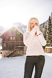 Woman enjoying hot beverage while standing near mountain house