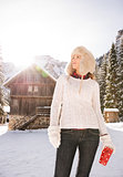 Woman in sweater looking up while standing near mountain house