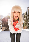 Cheerful woman with red cup standing near cosy mountain house